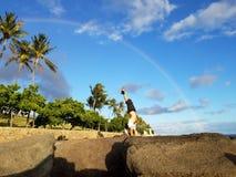 Man Handstanding on coastal rocks with Rainbow overhead. And coconut trees along path on Oahu, Hawaii Stock Photos