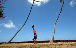 Man Handstanding in the grass along cliff shore next to shallow. Ocean waters of Waikiki with Coconut trees hang over looking into the pacific ocean at Leahi Stock Photos