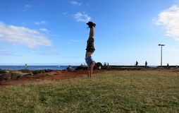 Man Handstands along shore of Magic Island. Man wearing shorts, shirt, and shoes Handstanding along shore of Magic Island with Ala Wai Boat Harbor, Waikiki Stock Image