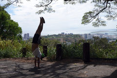 Man Handstands at Mountain lookout point above the City of Honol Stock Image