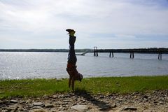 Man Handstands on rocky grassy beach with Pier. Man wearing a hat, aloha shirt, pants, and shoes Man Handstands on rocky grassy beach with Pier on Cousins Island Stock Image