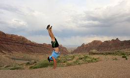 Man Handstands Spotted Wolf Canyon edge. Man wearing a hat, t-shirt, shorts, and slippers does Handstand on cliffs of Spotted Wolf Canyon with road leading Stock Photos