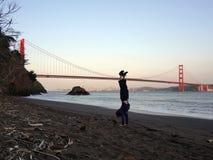 Man handstans på stranden framme av Golden gate bridge Arkivbilder