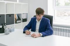 Man handstil i en anteckningsbok i kontoret Royaltyfri Bild