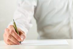 Man handstil med en reservoarpenna på tomt papper Arkivbilder