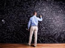 Man handstil på den stora svart tavla med matematiska symboler Royaltyfria Bilder