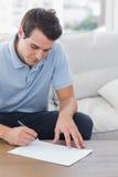 Man handstil på ett papper, medan han sitts på en soffa Royaltyfria Foton