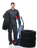 Man with handtruck and tires Stock Photo