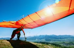Man with hang-glider starting to fly from the hill top stock image