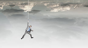 Man hang on rope Stock Images