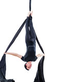 Man hanging in aerial silk, isolated on white. Background Royalty Free Stock Images