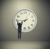 Man hanging on big clock hand Stock Photos