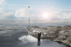 Man hanging on cliff with blank flag and sunlight cloudscapes Stock Image