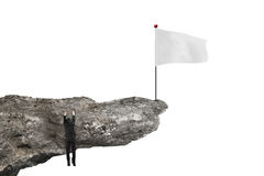 Man hanging on cliff with blank flag and white Stock Images
