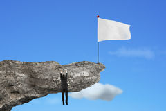 Man hanging on cliff with blank white flag and sky Stock Images