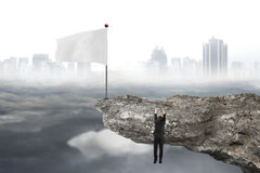 Man hanging on cliff with white flag and cloudy cityscape Royalty Free Stock Photo