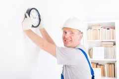 Man hanging clock Stock Images