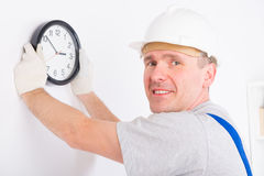Man hanging clock Stock Photography