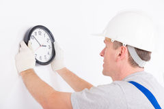 Man hanging clock Royalty Free Stock Photography