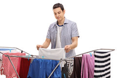 Man hanging clothes on a rack dryer Stock Photo