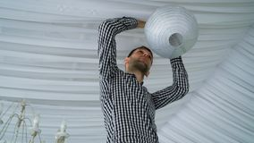 Man hanging colorful white pink gray paper lanterns to ceiling. royalty free stock images