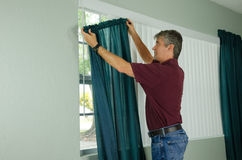 Man hanging curtains home repair maintenance. A handy man home repair service technician or home owner hanging curtains for the window treatment in a new house Royalty Free Stock Image