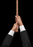 Man hanging at end of his rope. A man hanging at end of his rope on black Stock Images