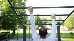A man hanging and goes through the horizontal bars on a sports ground. Mid shot stock video footage