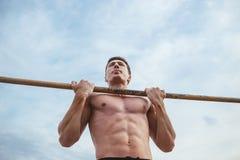 Man hanging on the horizontal bar Stock Photo