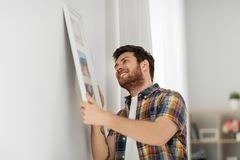 Man hanging picture in frame to wall at home. Interior decoration and renovation concept - smiling man hanging picture in frame to wall at home stock images