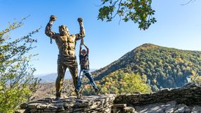 Man is hanging on prometheus sculpture on the backgroung of Ahun mountain, Sochi, Russia stock photo