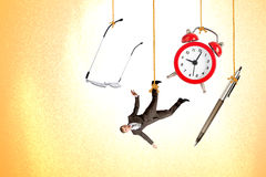 Man hanging on rope with clock, pen and glasses stock image