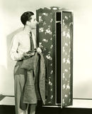 Man hanging up blazer in armoire stock images