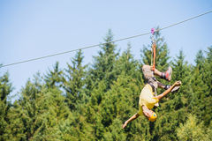 Man Hanging Upside Down On Zip Line. Full length of young man hanging upside down on zip line against trees in forest stock photo