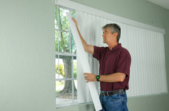 Man hanging vertical blinds home repair maintenance Royalty Free Stock Photography