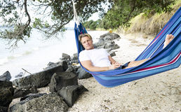 A man happily relaxing in a hammock on the beach. Royalty Free Stock Images