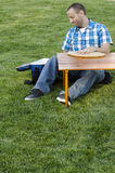 Man happy by the contents of his cooler. Man having a picnic outside in the grass at a small wooden table and a cooler and a cutting board Stock Photo