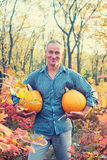 Man with happy face is carrying pumpkins Stock Image