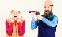 Man with happy face drills head of woman, white background. Builder, repairman makes hole in female head. Woman on scared face in helmet, hard hat. Husband royalty free stock photo