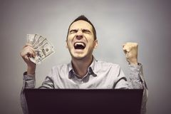 Man is happy in front of the computer to hold 500 dollars. Winning in an online casino. Profit from online stock trading. Easy money. Earnings on the Internet Royalty Free Stock Photos