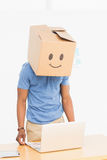 Man with happy smiley box over face in front of laptop Stock Photo