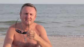 Man happy on vacation taking off glasses and sunbathing on the beach. stock video footage