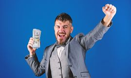 Man happy winner rich hold pile of dollar banknotes blue background. Easy cash loans. Win lottery concept. Businessman. Got cash money. Get cash easy and royalty free stock photography