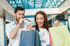Man and happy woman with credit card and shopping bags Royalty Free Stock Photos