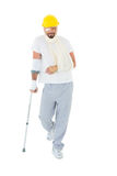 Man in hard hat with broken hand and crutch Royalty Free Stock Photo