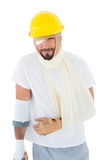 Man in hard hat with broken hand and crutch Stock Image