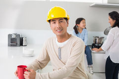 Man in hard hat with family in background at home Stock Image