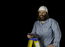 Man in hard hat holding a tablet on a step ladder Royalty Free Stock Photography