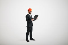 Man in hard hat looking at black folder in his arms. Serious man in a formal wear and hard hat looking at black folder in his arms Stock Photos
