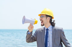 Man with hard hat and loudspeaker on beach Stock Image